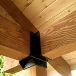 Timber framed overhang with custom brackets by Falkner Ironworks